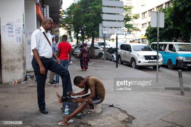 Shoe shiner cleans a commuters shoe on January 30, 2020 in Luanda, Angola. Businesswoman Isabel dos Santos is the daughter of the former President of...