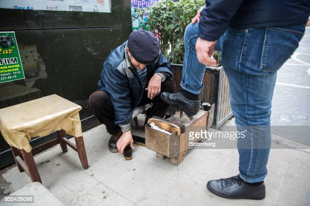 A shoe shiner polishes a customer's shoes in Baku Azerbaijan on Friday March 16 2018 Azerbaijan's economy barely returned to growth last year...