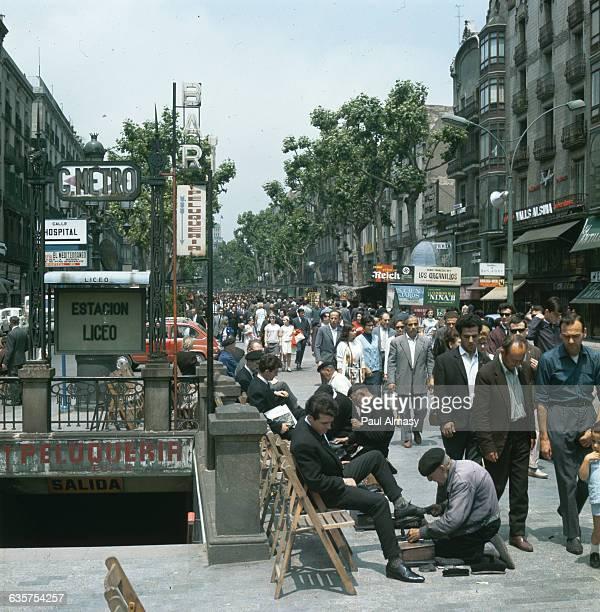 Shoe shiners work alongside the bustling treelined walkway of Ramblas de San Jose Barcelona Spain   Location Barcelona Spain