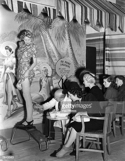 A shoe store offering a unique service by painting stockings on women's legs during the clothing rationing of World War II The sign reads 'No More...