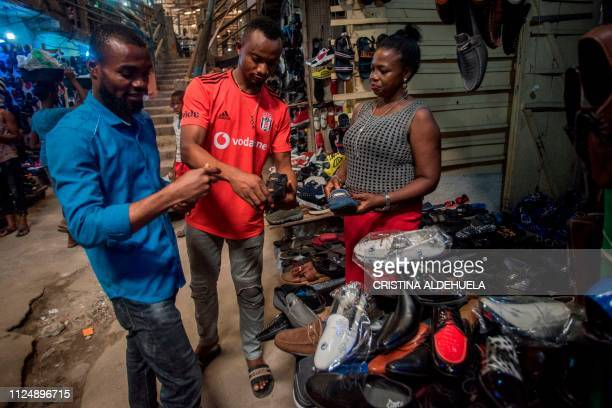A shoe vendor speaks to customers at a shop in the Ariaria International Market famous for shoe making and leather work in Aba a city in one of the...