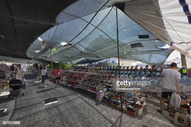 shoe vendor's section at alacati bazaar on a sunny day. - emreturanphoto stock pictures, royalty-free photos & images
