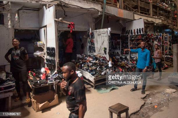 Shoe vendors stand next to shops of the Ariaria International Market famous for shoe making and leather work in Aba a city in one of the proBiafran...
