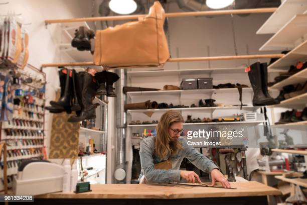 shoemaker cutting leather on workbench surrounded by shoes at workshop - surrounding stock pictures, royalty-free photos & images