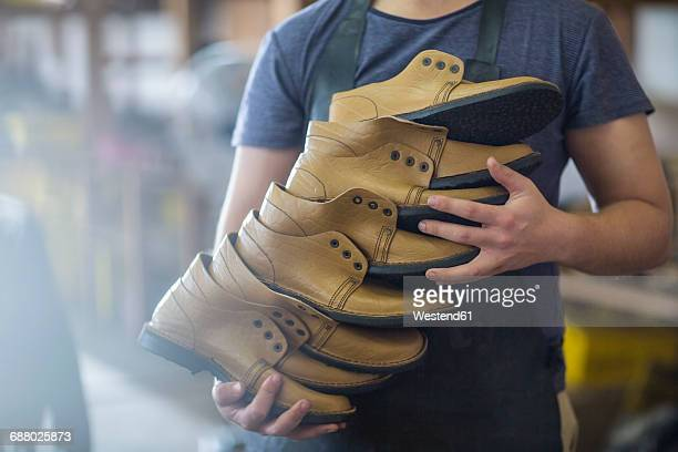 shoemaker holding stack of shoes - shoe factory stock pictures, royalty-free photos & images