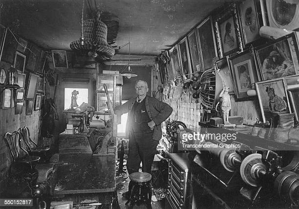 Shoemaker is shown with all his art on the walls and equipment in his well-used shop, circa 1900.