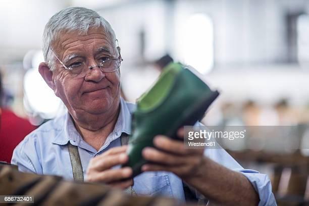 Shoemaker looking at shoelast in workshop