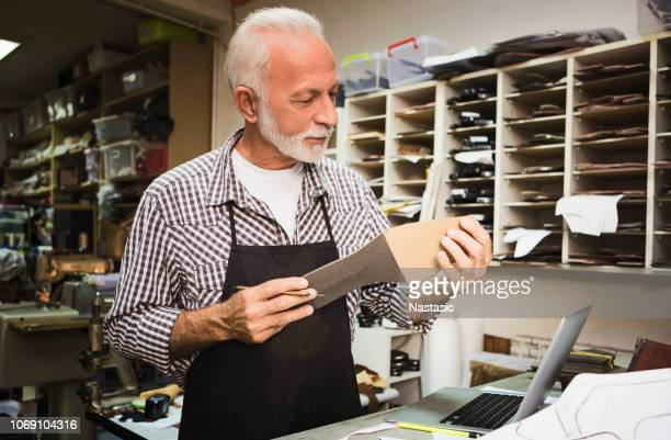 shoemaker making new boots in workshop - shoe factory stock pictures, royalty-free photos & images