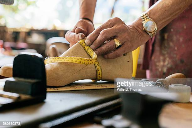 shoemaker measuring wooden shoe form - shoemaker stock photos and pictures