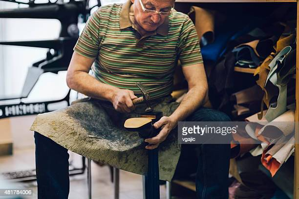 Shoemaker putting sole on shoe.