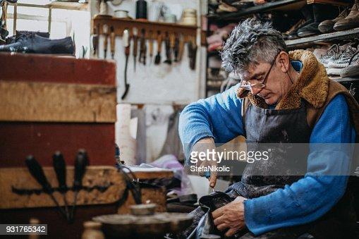 Shoemaker putting sole on shoe
