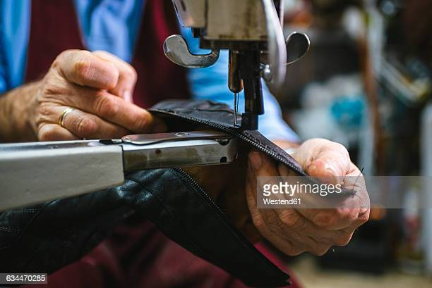 Shoemaker sewing a shoe with machine in his workshop, close-up
