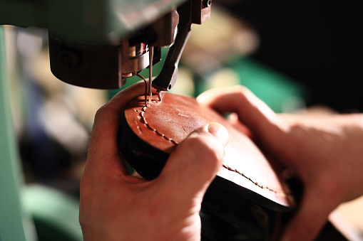 Shoemaker sews shoes 493181888