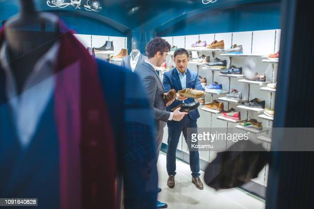 shoemaker showing new custom shoe design - shoe store stock pictures, royalty-free photos & images