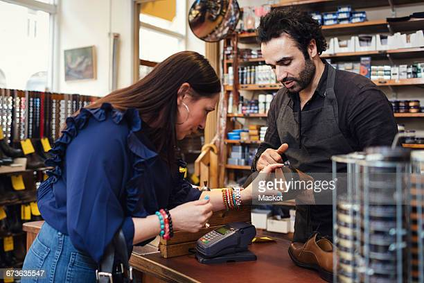 shoemaker showing shoe to female customer in store - shoemaker stock photos and pictures