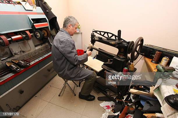 Shoemaker using sewing machine to repair old shue