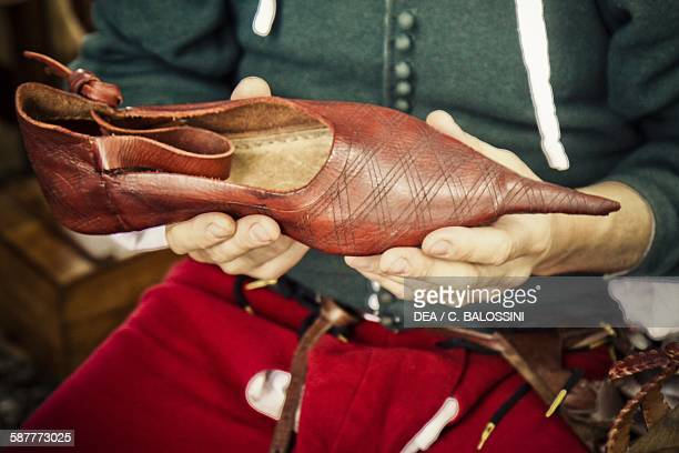 Shoemaker with a women's shoe, 14th century. Historical reenactment.