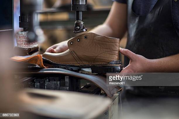 shoemaker working on shoe in workshop - shoemaker stock photos and pictures
