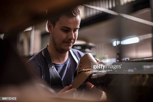 shoemaker working on shoe in workshop - leather shoe stock pictures, royalty-free photos & images