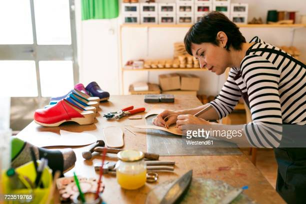 shoemaker working on template in her workshop - shoemaker stock photos and pictures