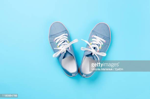 shoes against blue background - canvas shoe stock pictures, royalty-free photos & images