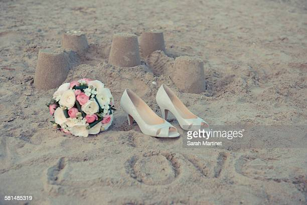 9519c29afaa1ce Shoes and bridal bouquet on the sand of the beach