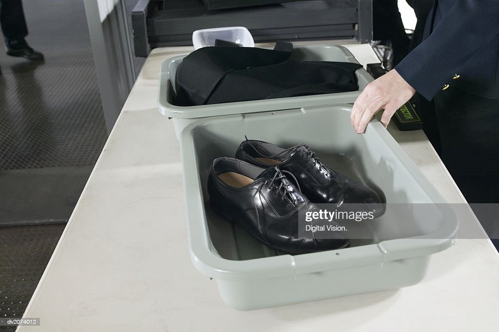 Shoes and Clothes in Containers on a table at Airport Customs : Stock Photo