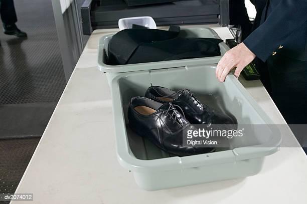 shoes and clothes in containers on a table at airport customs - servizio di sicurezza foto e immagini stock