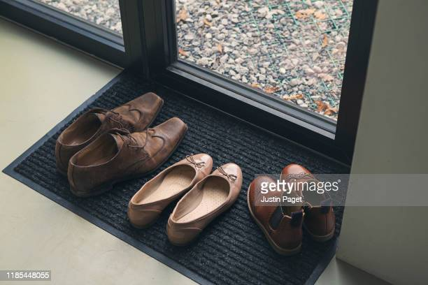 shoes by door - brown shoe stock pictures, royalty-free photos & images