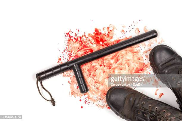 shoes by nightstick on messy blood over white background - truncheon stock pictures, royalty-free photos & images