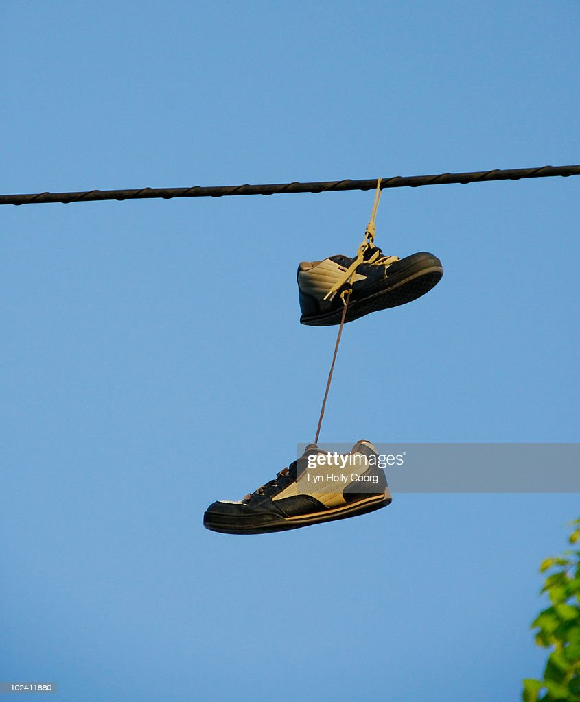 Shoes hanging on power line : Stock Photo