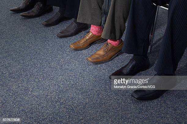 Shoes of businesspeople sitting side by side
