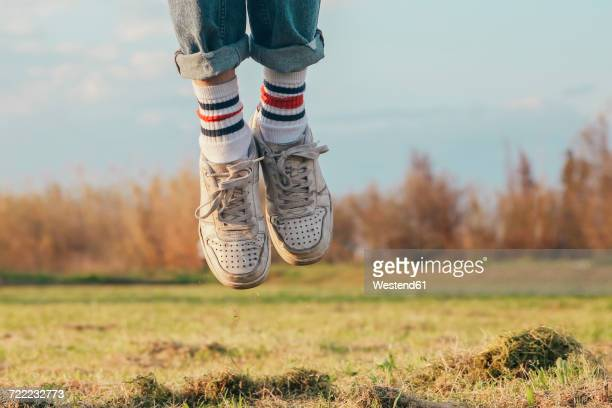shoes of man jumping on meadow - men in white socks fotografías e imágenes de stock