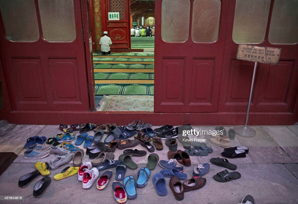 Shoes of worshippers are seen at the door as Chinese Muslims of the Hui ethnic minority pray before breaking fast during the holy fasting month of Ramadan at the historic Niujie Mosque on July 3, 2014 in Beijing, China. The Hui Muslim community, which numbers more than an estimated 10 million throughout the country, is predominantly Chinese-speaking. Muslims around the world are marking Ramadan, where the devout fast from dawn until dusk, and is a time of fasting, prayer and charitable giving.