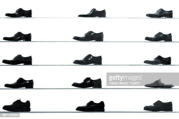 Shoes On Shelves Against White Wall