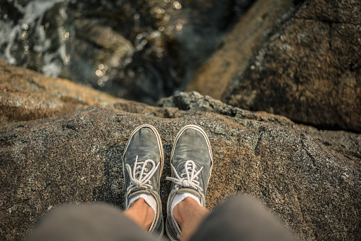 Shoes standing on the edge of cliff over ocean 849034226