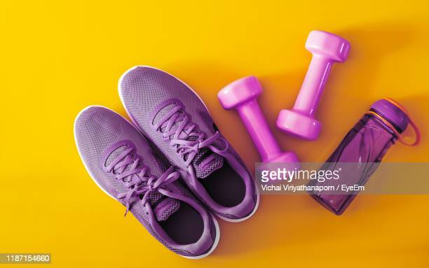 shoes with dumbbell and bottle on yellow background - purple shoe stock pictures, royalty-free photos & images