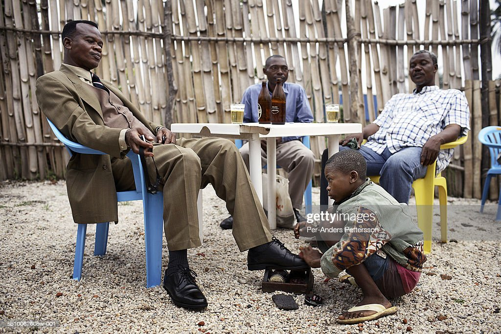 Shoeshine boy cleans shoes for businessman in bar : News Photo