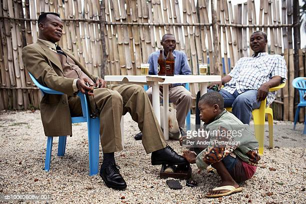 A shoeshine boy cleans a pair of shoes for a businessman in a bar on March 4 2006 in Kisangani in Congo DRC Kisangani is a port city along the The...