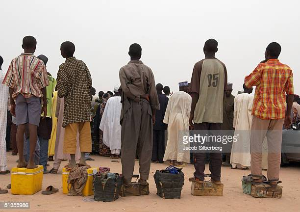 Shoeshine boys and drink sellers struggle for a view of the action on March 17 2004 at the Argungu Fishing Festival in Argungu Nigeria The Argungu...