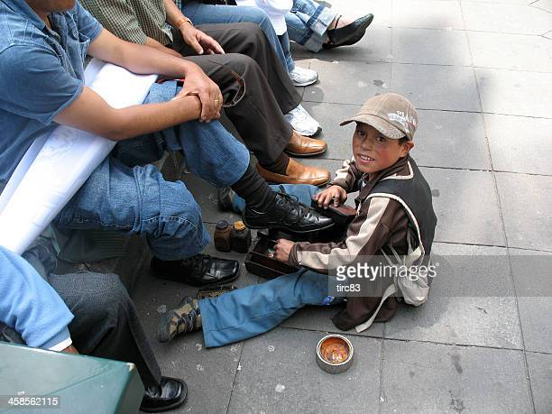 Shoeshine boys at work in the main square of Quito