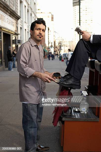 Shoeshine man with customer on sidewalk, portrait