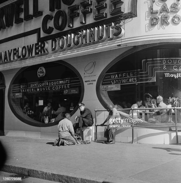 Shoeshine outside a diner selling Mayflower doughnuts and Maxwell House coffee on Broadway, New York City, 1948.
