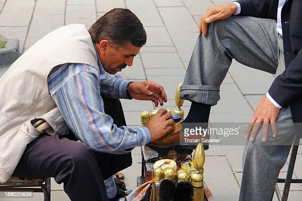 Shoeshiner at work on the street. Other keywords: Turkish man, street, shoeshining, boot polisher, market, shoe shiner, commerce, stall, working,...