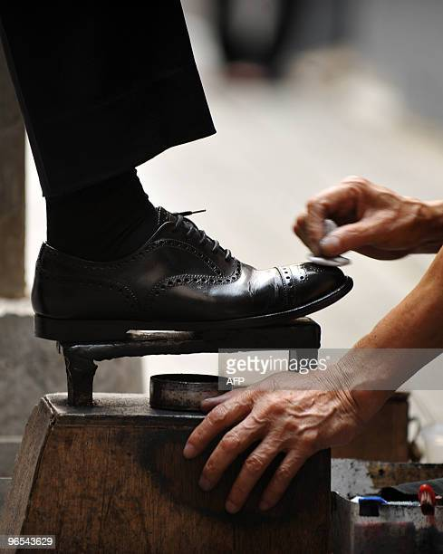 A shoeshiner cleans a businessman's shoes along a street in the Central district of Hong Kong on June 19 2009 Shoeshiners who for years worked...