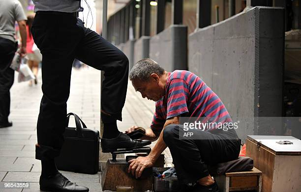 Shoeshiner Yeung SiuYing cleans a businessman's shoes along a street in the Central district of Hong Kong on June 19 2009 Shoeshiners who for years...