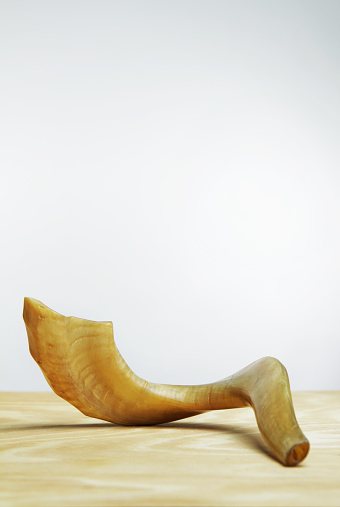 Shofar on wooden table in front of white wall 186885162