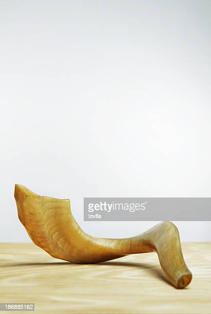 Shofar on wooden table in front of white wall