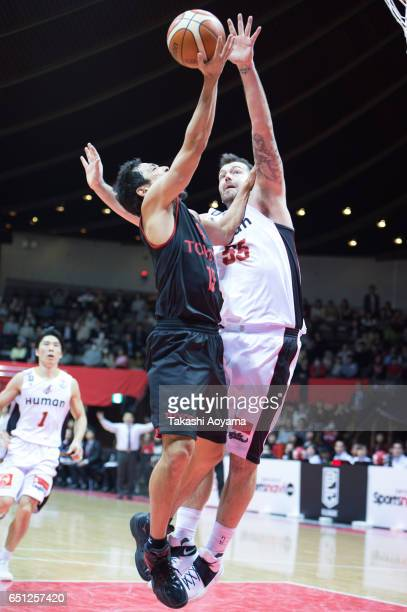 Shohei Kikuchi of the Alvark Tokyo tries to shoot under pressure from Josh Harrellson of the Osaka Evessa during the B League match between Alvark...
