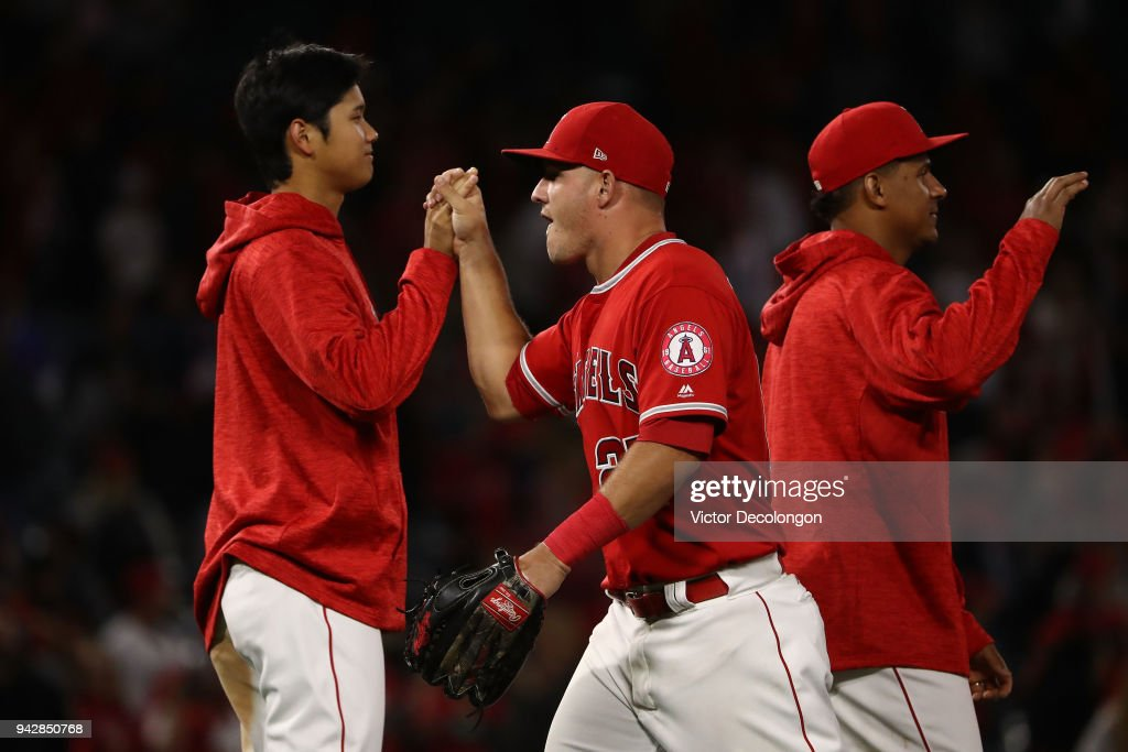 Shohei Ohtani #17 and Mike Trout #27 of the Los Angeles Angels of Anaheim high five after the MLB game at Angel Stadium on April 6, 2018 in Anaheim, California. The Angels defeated the Athletics 13-9.